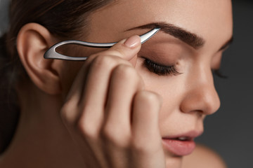 Woman With Closed Eyes And Tweezers For Eyebrows. Beauty Tools