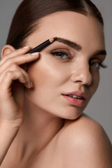Beautiful Sexy Woman Contouring Eyebrows. Glamorous Makeup
