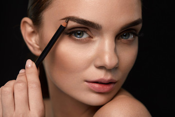 Beautiful Woman Contouring Eyebrows With Pencil. Beauty