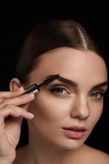 Beautiful Woman Brushing Eyebrows With Brush. Beauty