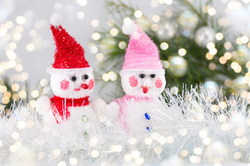 Two toy snowman with festive background