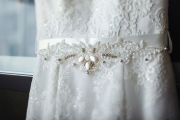 Stylish vintage white wedding dress on hanger  closeup