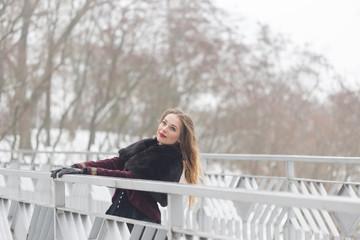 beautiful girl standing on the pedestrian bridge in winter
