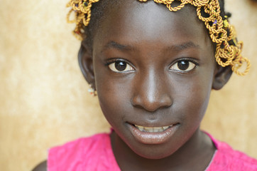 Gorgeous Black Beautiful Girl Showing Herself as a Proud African Symbol. Little African Girl Smiles Happily at the Camera.