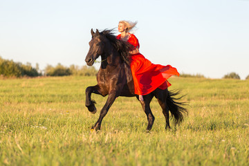 Beautiful lady in red riding black horse.
