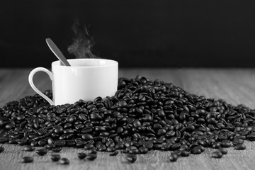 Cup of coffee in pile of seeds of coffee on brown plate / Blurred and Select focus image, black and white