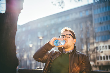 Man sitting on park bench and drinking water