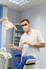 Young man dentist in protection gloves and a mask