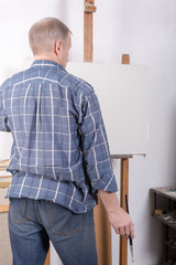 An artist painting on white canvas in studio