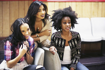 Young women together hanging out at bowling alley