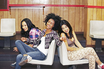 Three young women hanging out at a bowling alley
