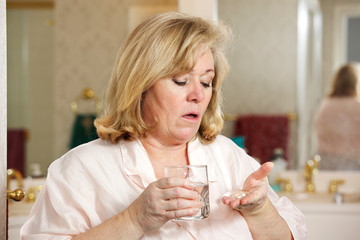 Mature woman's morning routine - holding medicine and water