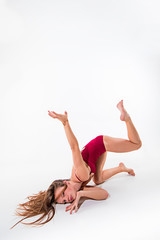 Young beautiful dancer in beige dress dancing on white background