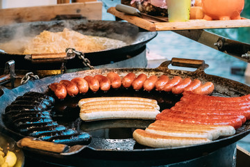 Potatoes And Sausages Fried On A Frying Pan. Traditional Christmas Dish Of Street Food On Streets Of Europe