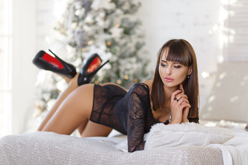 Sexy woman with dark hair in a lace bodysuit lying on the bed. In the background, tree, garlands. New Year, Christmas.
