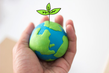 globe on hand with plant, safe the world , ecology concept