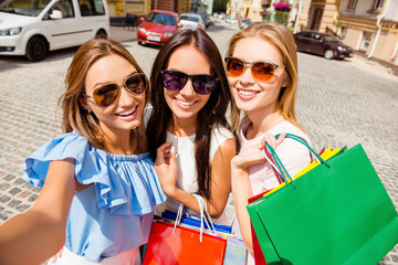 Attractive happy girlfriends making selfie with shopping bags