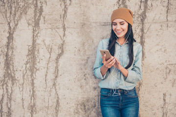 Portrait of happy trendy woman in cup listening music on mobile