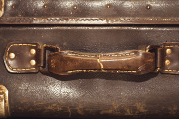 ripped handle of vintage leather suitcase. closeup. selective focus