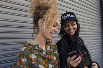 Smiling young women looking at a cell phone