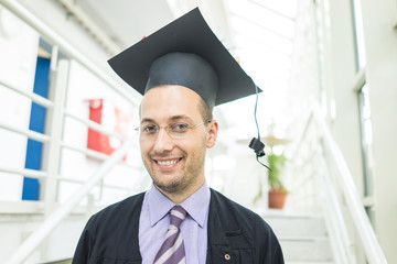 Young male student in black graduation gown