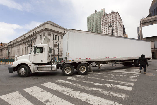 Huge white semi truck negotiating New York City intersection. Horizontal.