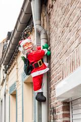 Santa hanging on the drainpipe