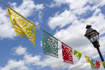 Colorful diagonally spanning Tibetan prayer flags against blue sky with lamppost.
