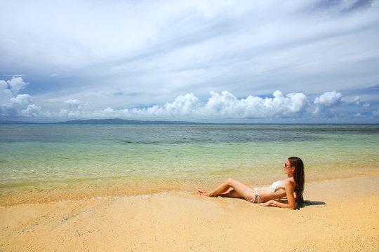 Young woman in bikini lying on the beach on Taveuni Island, Fiji