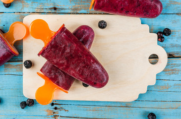 Delicious home-made popsicles of black currant. On a wooden table, copy space