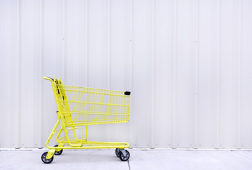 Yellow shopping cart on sidewalk against gray / grey wall. Horizontal.