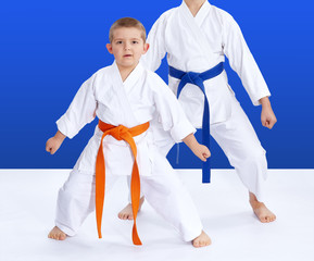 Two athletes on a blue background in the rack of karate