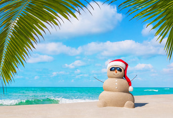 Sandy Snowman in Christmas Santa hat and sunglasses at ocean tropical palm beach