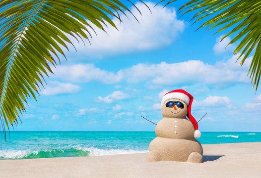 Sandy Snowman in Christmas Santa hat and sunglasses at ocean tropical palm beach