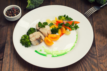 Boiled seabass with steamed vegetables - totally healthy meal. Top view. Close-up