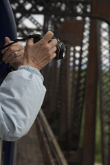 Woman taking a picture from a train as it crosses a railroad bridge