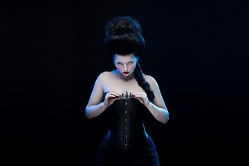 brunette woman with high hair, crown and corset in old style on a black background