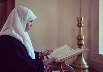 Muslim woman reading Koran and praying in mosque