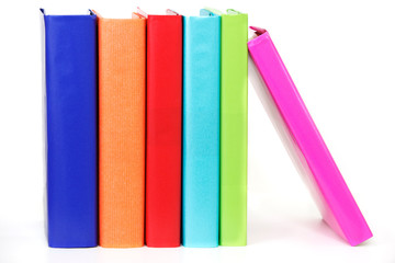 Row of colorful books proped up by one leaning on the end