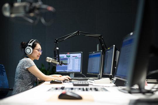 young woman dj works in modern broadcast studio