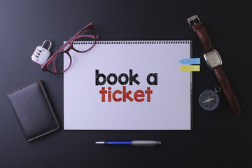 Travel concept with notebook written book a ticket with passport