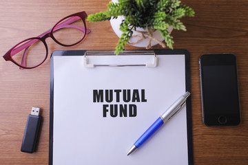 Office desk with a paper written MUTUAL FUND with pen, glass