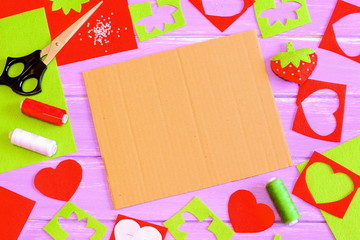 Sewing handicraft background. Felt strawberry toy, scissors, red and green felt sheets and scraps, thread, needle, paper pattern, beads on wooden background. Cardboard sheet with copy space. Top view