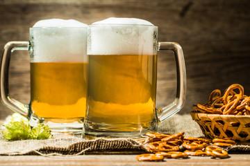 Two beer mugs with hops and pretzels on linen cloth