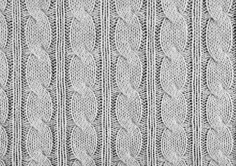 Grey knitted textured background with a pattern closeup