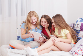 happy girls with smartphone and tablet pc at home
