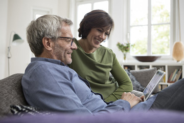 Smiling mature couple at home on the sofa sharing tablet