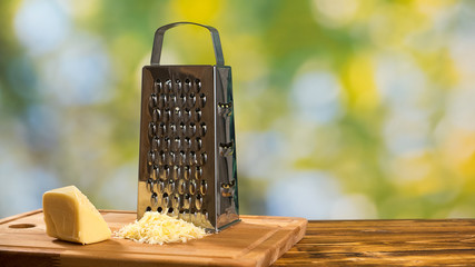 Grater and parmesan cheese on the wooden table