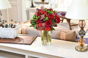 Букет из красных роз в стеклянной вазе на фоне красивого интерьера