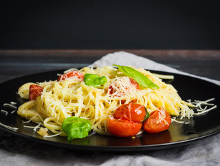 Pasta with tomatoes and basil on the dark background. Shallow depth of field.